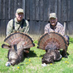 Two men pose with their turkeys at Long Creek Outfitters