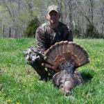 A man poses with his turkey at Long Creek Outfitters
