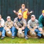 Several men pose with their deer at Long Creek Outfitters