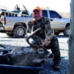 A hunter poses with his deer at Long Creek Outfitters