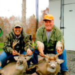 Two men pose with their deer at Long Creek Outfitters