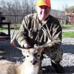 A man poses with his deer at Long Creek Outfitters